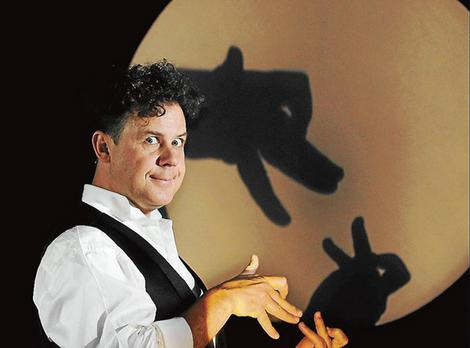 Raymond Crowe making shadow puppets as part of his stage act.